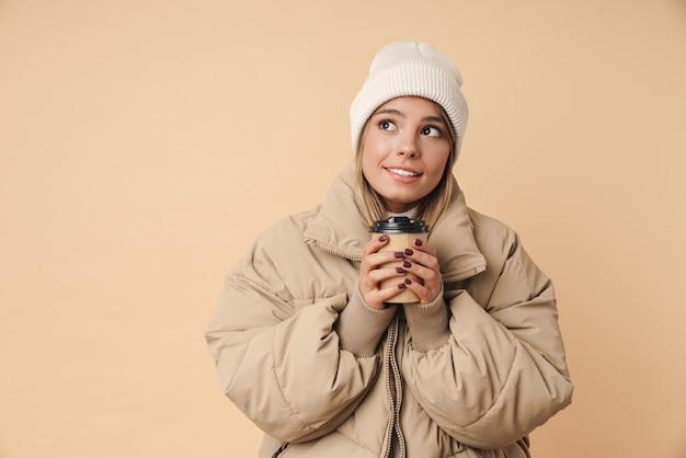 Портрет красивой молодой женщины в зимнем пальто, держащей бумажный стаканчик и смотрящей в сторону