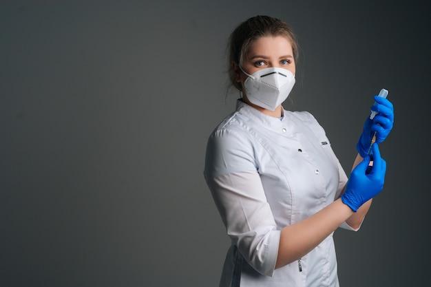 Портрет медсестры в синих перчатках и лицевой маске, держащей и заполняющей вакцину для шприца на черном изолированном фоне, глядя в камеру. врач готовится ввести вакцину от коронавируса.
