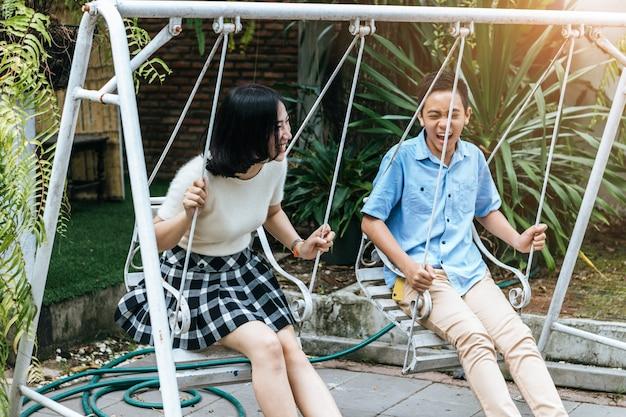 Портрет другой сестры и младшего брата, играя качели и улыбаясь вместе