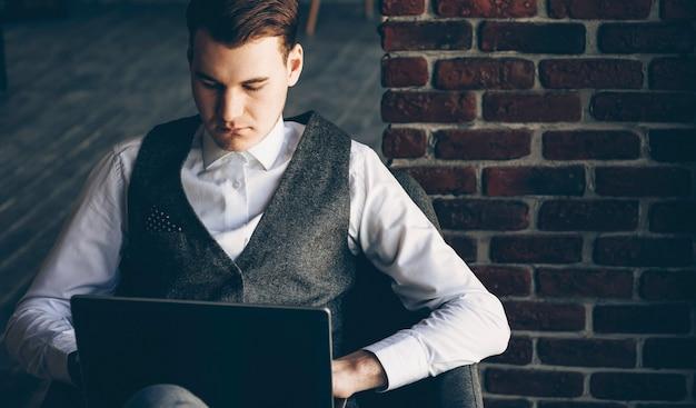 Портрет молодого стильного делового человека, работающего за своим ноутбуком, сидя в своем офисе рядом с вдвоем серьезно.
