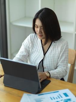 Портрет деловой женщины, работающей с цифровым планшетом и бизнес-диаграммой на деревянном столе