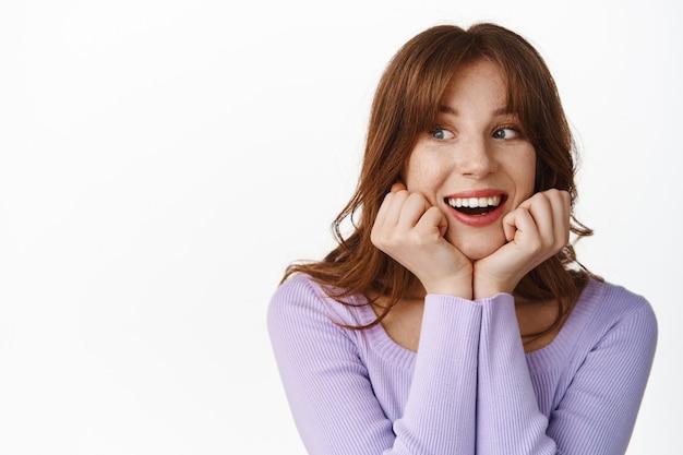 赤毛のかわいい女の子の肖像画、白に興味と期待を持ってちらっと見ている幸せと笑顔の白い歯