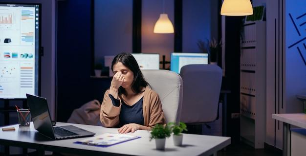 중요한 작업을 완료하기 위해 초과 근무를 하는 직장에서 스트레스를 받는 초상화. 직원은 중요한 회사 프로젝트를 위해 사무실에서 혼자 밤늦게까지 일하다가 잠이 듭니다.