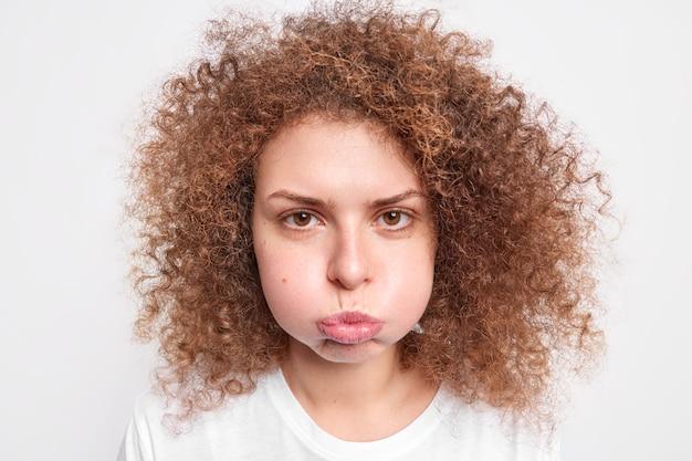 気分を害した縮れ毛の美しい若い女性の肖像画が頬を吹く不快な表情は白い壁に孤立した否定的な感情を表現しています。人間の顔の表情と感情