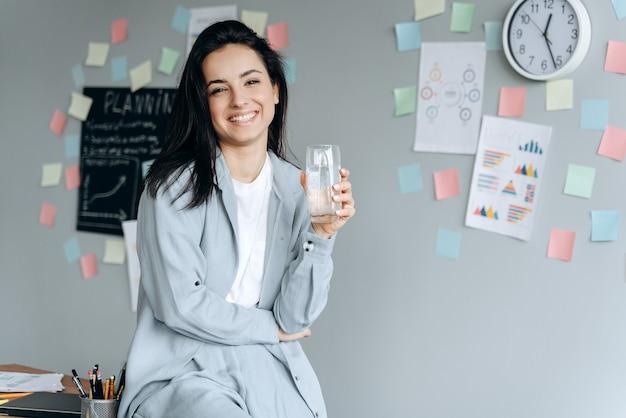 Портрет офисного работника, держащего стакан воды, смотрящего в камеру