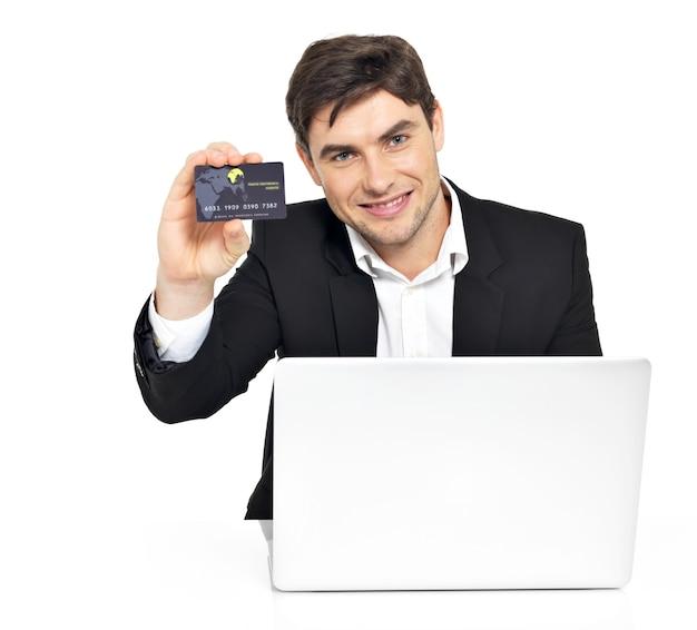 Портрет офисного работника с ноутбуком и кредитной картой, сидя на столе, изолированном на белом.