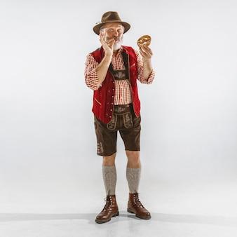 伝統的なバイエルンの服を着て、帽子をかぶったオクトーバーフェストの年配の男性の肖像画。白い背景の上のスタジオで男性のフルレングスのショット。お祝い、休日、お祭りのコンセプト。パフを食べる。