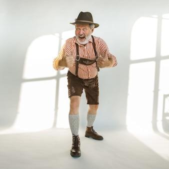 伝統的なバイエルンの服を着て、帽子をかぶったオクトーバーフェストの年配の男性の肖像画。白い背景の上のスタジオで男性のフルレングスのショット。お祝い、休日、お祭りのコンセプト。素敵なジェスチャー。