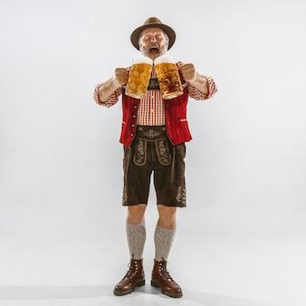 伝統的なバイエルンの服を着て、帽子をかぶったオクトーバーフェストの年配の男性の肖像画。白い背景の上のスタジオでの男性のフルレングスのショット。お祝い、休日、お祭りのコンセプト。ビールに誘う。