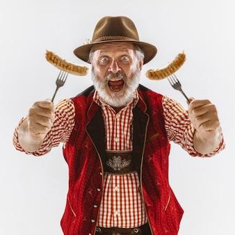 伝統的なバイエルンの服を着て、帽子をかぶったオクトーバーフェストの年配の男性の肖像画