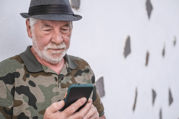 Портрет старого привлекательного старшего человека с грустным выражением лица с помощью мобильного телефона. белое лицо с бородой. изолированные на белом фоне