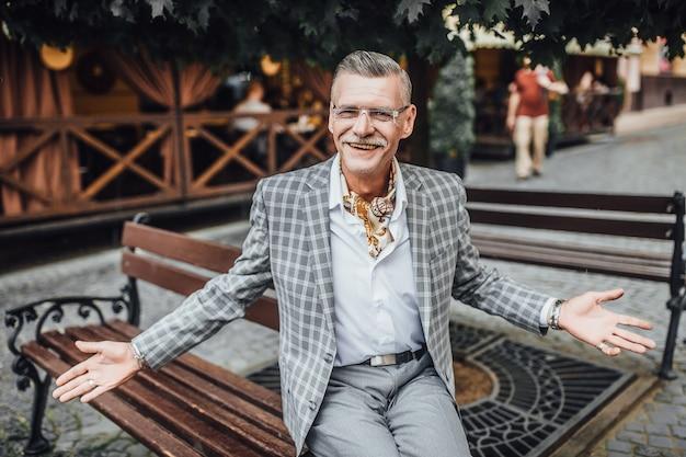 Портрет старого бородатого туриста в сером костюме и улыбке