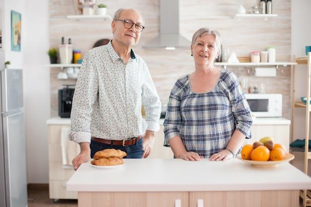 朝食の準備をしながらキッチンでカメラをのぞき込む陽気な老夫婦の肖像画。幸せな引退した男と女。