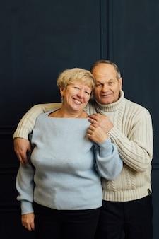 抱きしめて笑っている老夫婦の妻と夫の肖像画。濃い青の背景。引退の幸せな恋人たち。エイジズムをやめなさい。 。高品質の写真