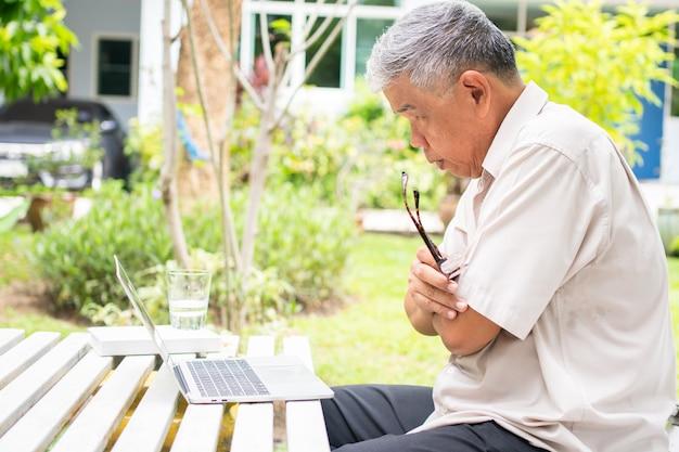 은퇴 후 새로운 기술을 배우기 위해 뒤뜰에서 컴퓨터 노트북을 사용하는 노인 아시아 남성의 초상화. 연령차별이 없고 학습에 늦지 않는다는 개념.