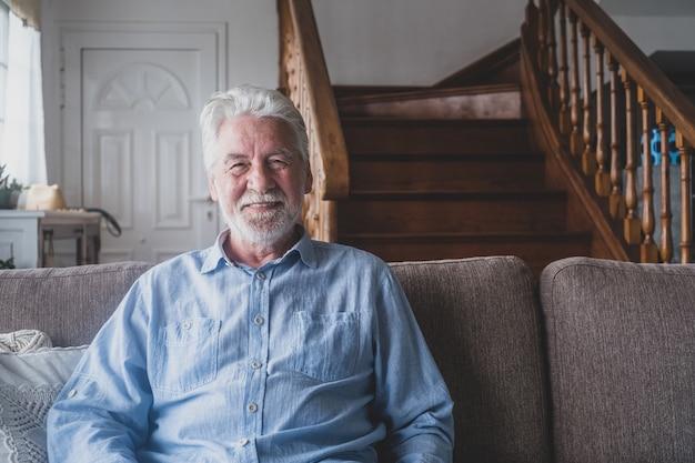 笑顔で自宅からソファに座っているカメラを見ている老人の肖像画。クローズアップ男性人シニア陽気な屋内。
