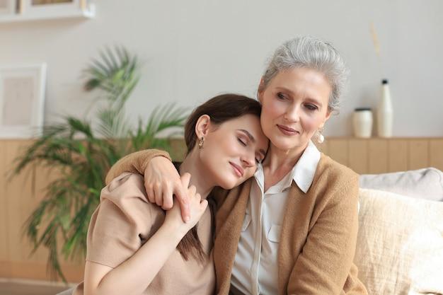 家で抱き締める老母と成熟した娘の肖像画。幸せな先輩のお母さんとソファで愛を抱きしめる大人の娘。