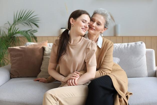 집에서 껴안고 있는 늙은 어머니와 성숙한 딸의 초상화. 행복한 시니어 엄마와 성인 딸이 소파에서 사랑으로 껴안고 있습니다.