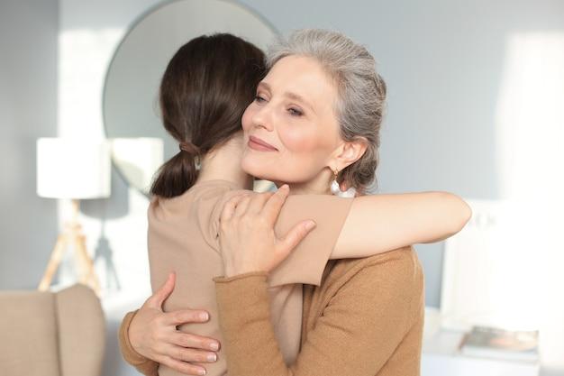 집에서 껴안고 있는 늙은 어머니와 성숙한 딸의 초상화. 행복한 신뢰 관계. 가족 개념입니다.