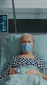 병원 병동에 안면 마스크를 쓴 노인 환자의 초상화