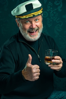 Портрет старика в роли капитана в черном свитере и шляпа, пьющая коньяк на черной студии