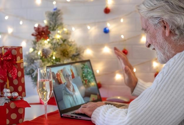 Портрет пожилого старшего мужчины, использующего ноутбук для видеозвонка с далекими людьми, празднующими рождественское мероприятие с бокалом игристого вина и улыбаясь. подарочная коробка и новогодняя елка