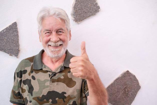 Портрет старого старшего оптимистичного человека, улыбающегося, делая положительный знак с большим пальцем руки вверх. белое лицо выражает нормальный жест