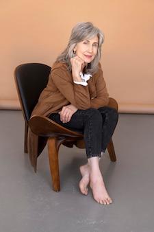 의자에 앉아 있는 나이든 우아한 여성의 초상화