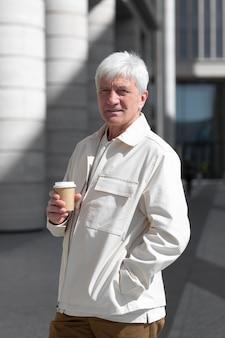 Портрет пожилого мужчины на открытом воздухе в городе, держащего чашку кофе
