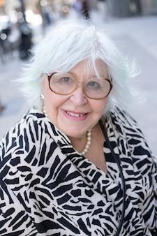 회색 머리를 하고 야외에서 카메라를 보며 미소를 짓고 있는 노부인의 초상화