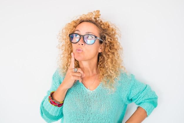 생각하고 꿈꾸는 한 아름다운 곱슬머리 여성의 초상화 - 흰색 배경에 안경과 파란색 셔츠를 입은 꿈꾸는 사람들의 클로즈업