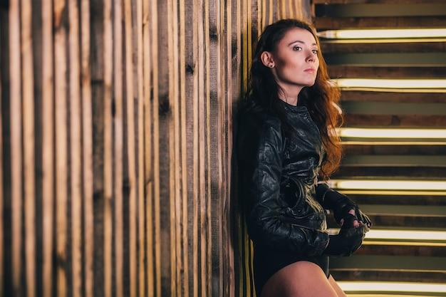 Портрет одной красивой чувственной сексуальной серьезной молодой страстной брюнетки с длинными волосами в кожаной черной куртке и в шортах Premium Фотографии