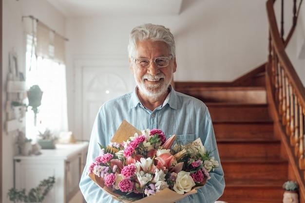 彼の妻やガールフレンドに与えるために花を持っている一人の幸せでかわいい老人の肖像画。バレンタインデーの贈り物やプレゼントを楽しんで家でカメラを見ているシニア