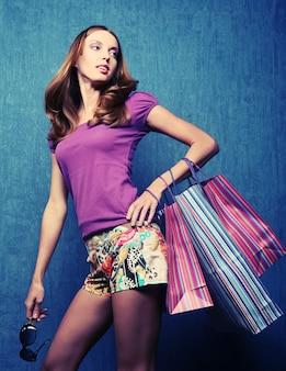 色付きのバッグを持つ1人の幸せな若い大人の女の子の肖像画