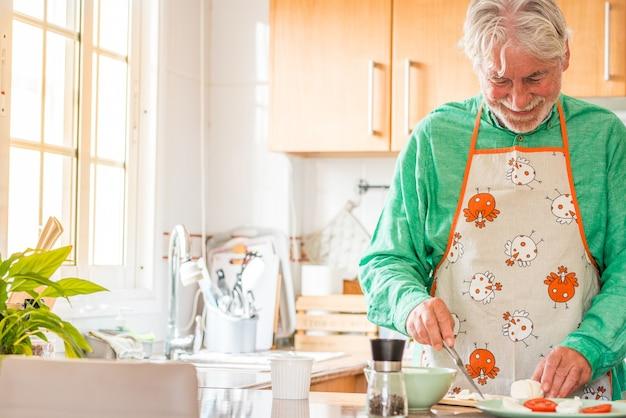 笑顔でキッチンで自宅で料理をしている一人の成熟した老人の肖像画。シニアは屋内で一人で昼食をとるために食事を準備しています。引退した男性学習料理人