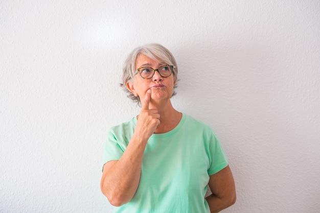 집에서 훌륭하고 좋은 아이디어를 생각하고 찾는 성숙한 노부인의 초상화