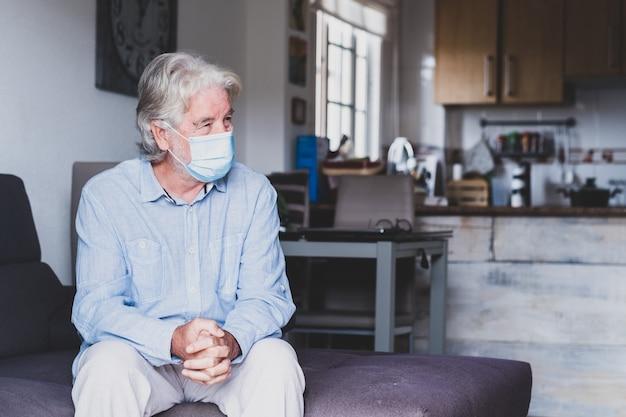 실내에서 코로나바이러스를 예방하기 위해 마스크를 쓰고 소파에 앉아 있는 한 노년의 초상화 - 집에서의 생활 방식