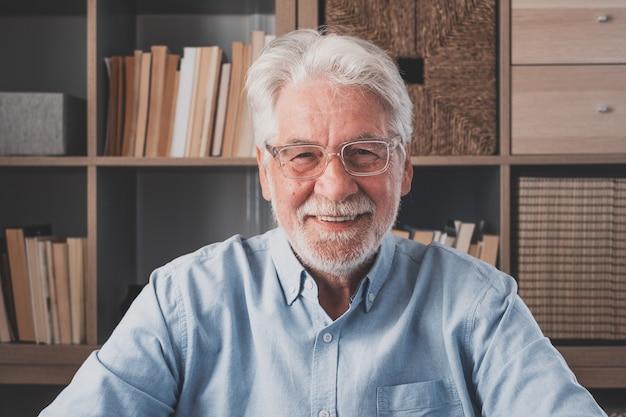 Портрет одного старого жизнерадостного старшего мужского пола, улыбаясь, весело дома. зрелый кавказский человек изучает независимые, глядя в камеру и позирует для картины.