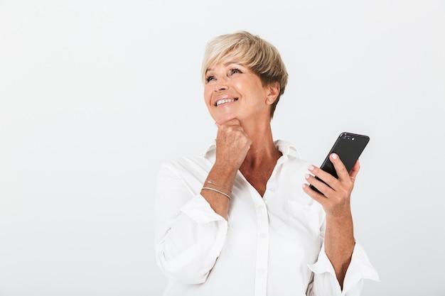 コピースペースで微笑んで、スタジオで白い壁に隔離された携帯電話を保持している短いブロンドの髪を持つ楽観的な大人の女性の肖像画