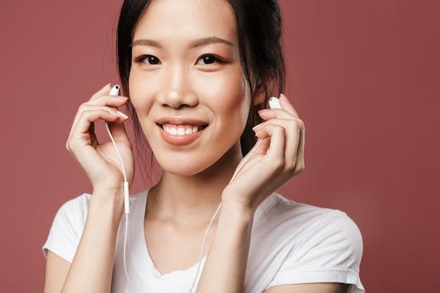 기본 복장을 한 낙관적인 아시아 여성의 초상화는 웃고 있고 빨간 벽에 격리된 이어폰으로 음악을 듣고 있습니다