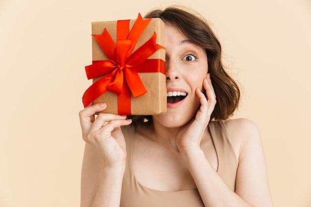 Портрет оптимистичной кавказской женщины 20-х годов, одетой в повседневную одежду, улыбающейся, держащей в руках подарочную коробку