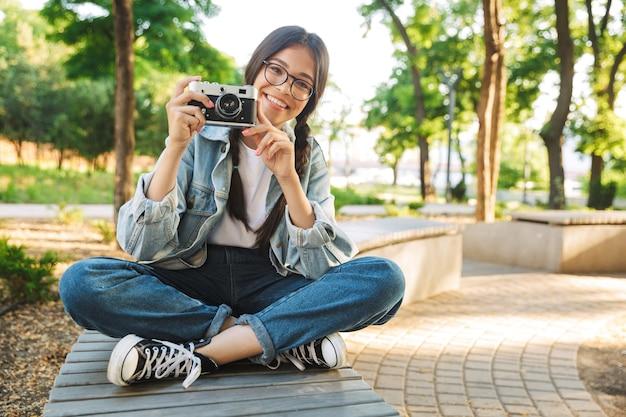 カメラを保持している自然公園の屋外のベンチに座って眼鏡をかけて楽観的な陽気な幸せなかわいい若い学生の女の子の肖像画