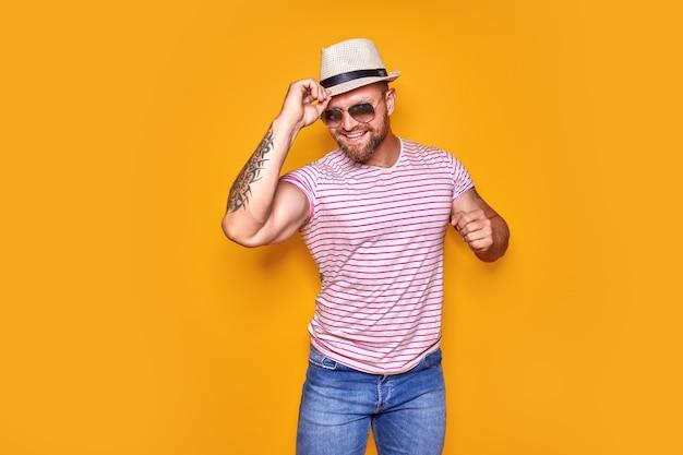 낙관적인 펑키 가이 댄스의 초상화는 노란색으로 격리된 여름 모양의 밀짚 모자 선글라스를 착용합니다.