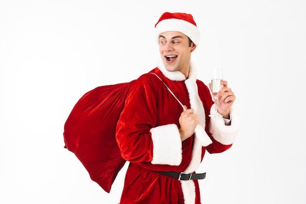 Портрет оптимистичного мужчины 30-х годов в костюме санта-клауса и красной шляпе, держащего подарочный пакет и бокал с шампанским