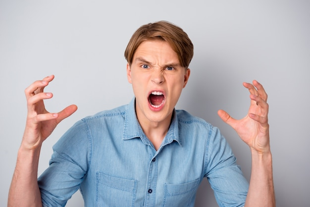 Портрет возмущенного мужчины, не согласного со своим другом, крикнуть, достаточно поднять руки, носить современную одежду, изолированную над стеной пастельных тонов