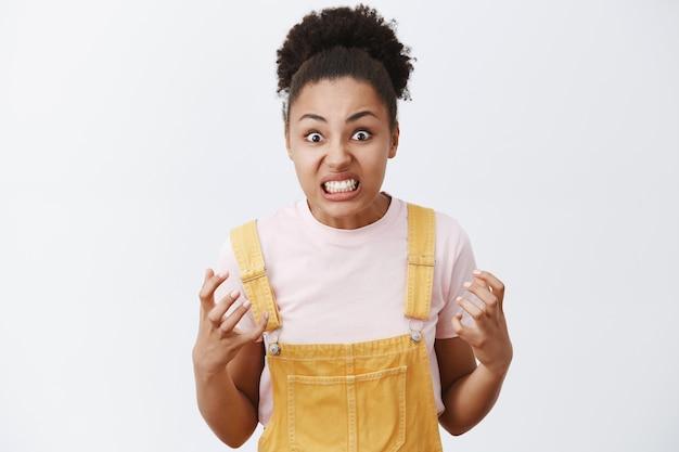 Портрет возмущенной, рассерженной и сердитой симпатичной темнокожей женщины с афро-прической, сжимающей кулаки и смотрящей с ненавистью