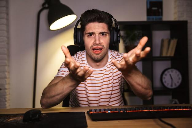 Портрет возмущенного молодого человека с наушниками, сидящего за столом с компьютером в комнате и жестикулирующего на камеру
