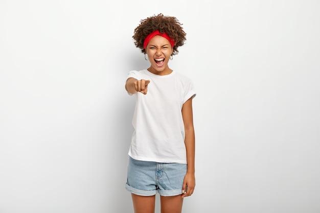 기뻐 한 아프리카 여성의 초상화는 재미있는 것을 웃고 카메라를 직접 가리키며 좋은 감정을 표현하고 빨간 머리띠, 티셔츠 및 반바지를 입고 흰 벽 위에 모델을 착용합니다.