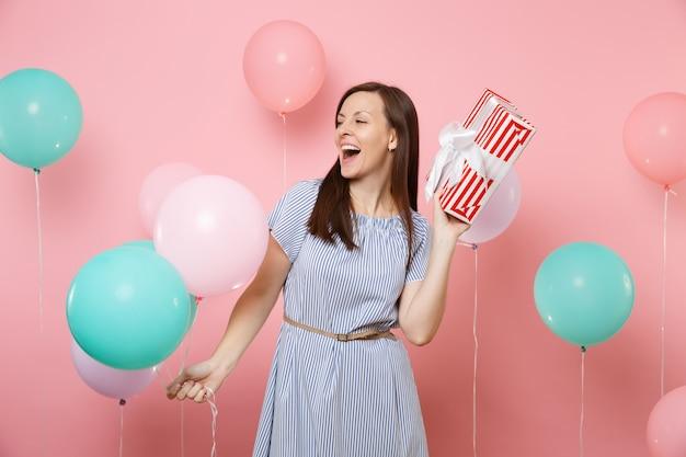 밝은 분홍색 배경에 선물 선물과 화려한 공기 풍선이 있는 빨간 상자를 옆으로 들고 있는 파란 드레스를 입고 기뻐하는 아름다운 여성의 초상화. 생일 휴일 파티 개념입니다.
