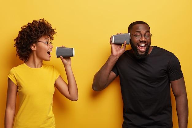 大喜びの黒人女性と男性の肖像画は使い捨てのコーヒーカップを保持します